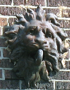 Cast iron lion's head wall anchor for marquee support.