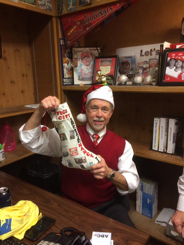 Jerry Gibbs, owner of J&E Office City, with it present from Santa Friday night at the Maplewood Christmas Tree Walk.