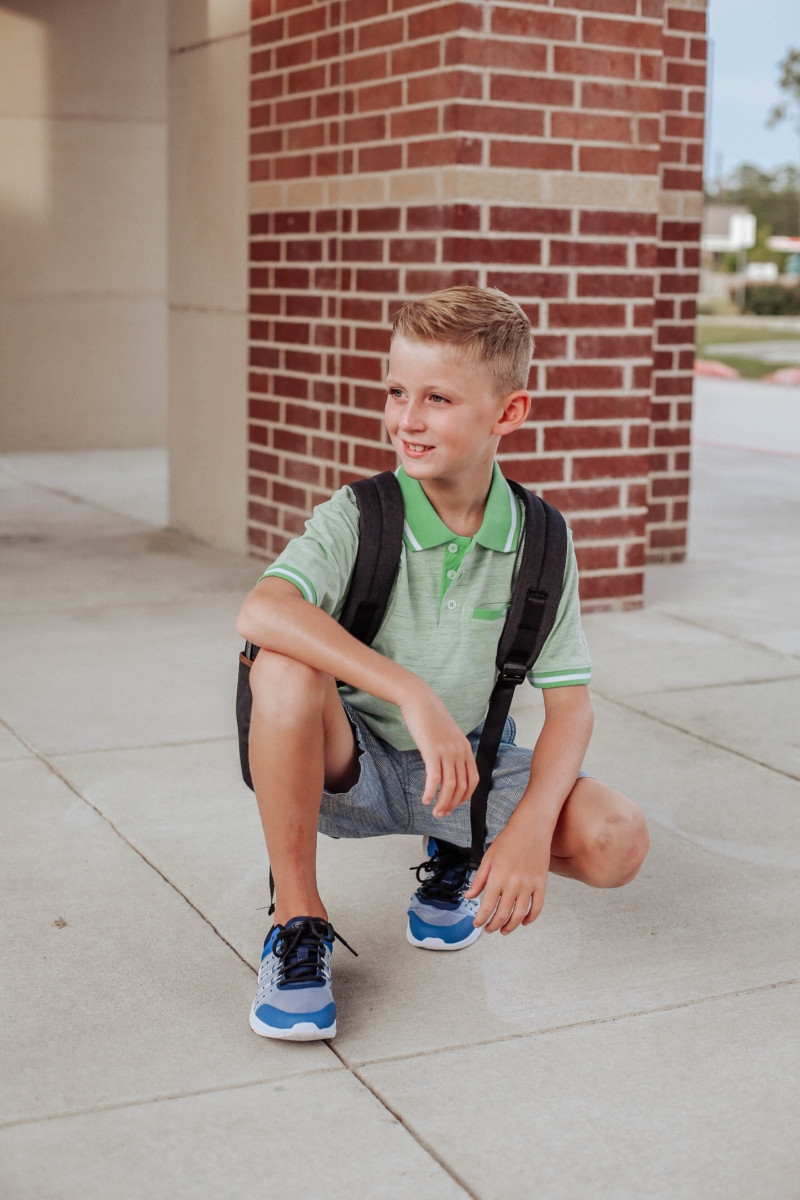 walmart back to school | Walmart Back To School Shopping by popular Florida fashion blog, Haute and Humid: image of boy standing in front of his school and wearing Walmart Athletic Works Boys' Slip On Cage Athletic Shoes, green Wonder Nation Short Sleeve Stretch Jersey Polo, and Wonder Nation Rib Waist Pull on Short.