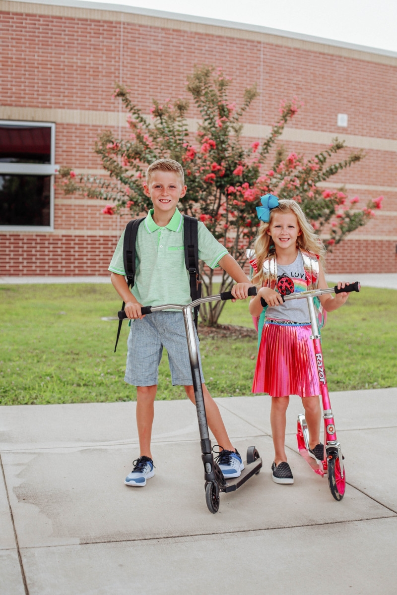 back to school | Walmart Back To School Shopping by popular Florida fashion blog, Haute and Humid: image of a boy and girl wearing Walmart back- to-school outfits and standing on their scooters in front of their elementary school. The girl is wearing a Walmart 365 Kids From Garanimals Flutter Graphic Tank Top, 65 Kids From Garanimals Shimmer Foil Pleated Skirt, and Wonder Nation Solid and Printed Bike Shorts, 2-Pack. The boy is wearing Walmart Athletic Works Boys' Slip On Cage Athletic Shoes, green Wonder Nation Short Sleeve Stretch Jersey Polo, and Wonder Nation Rib Waist Pull on Short.