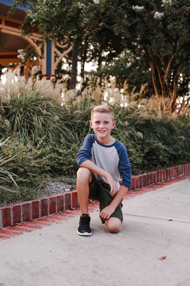 boys fall clothing | How to Get to School on Time: 7 Easy Ways by popular Houston blog, Haute and Humid: image of a boy standing outside and wearing a Tucker and Tate Baseball T-Shirt, Tucker and Tate Knit Shorts, and Nike Free Run 5.0 Sneaker.