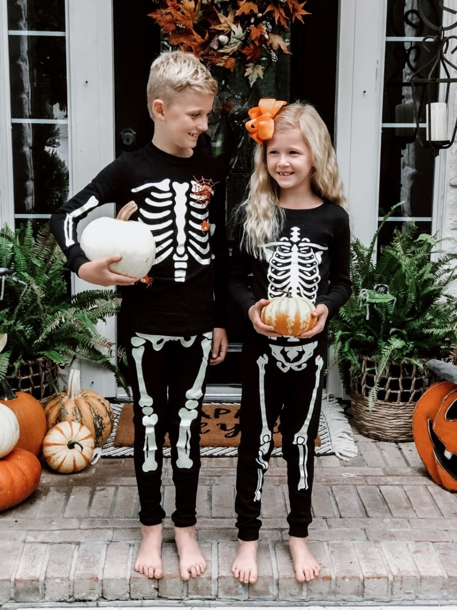 halloween party food | Easy Halloween Activities for Families by popular Houston lifestyle blog, Haute and Humid: image of two kids holding pumpkins on a front porch with a Target Project 62 Chevron Woven Area Rug, Etsy Happy Fall Yall Welcome Doormat, and wearing Amazon Little Pajamas skeleton glow-in-the-dark pajama sets.