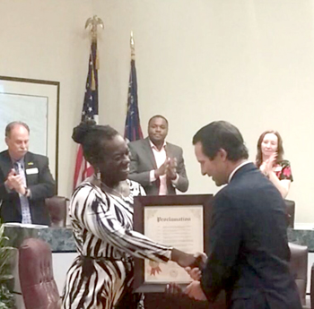 """Mayor David Lockhart presents Cricket Hall of Famer Petula Samuels with a proclamation which declared Tuesday, March 8, 2016, as """"Petula Samuels Day in Forest Park"""". Looking on are some of the City's Council Members."""