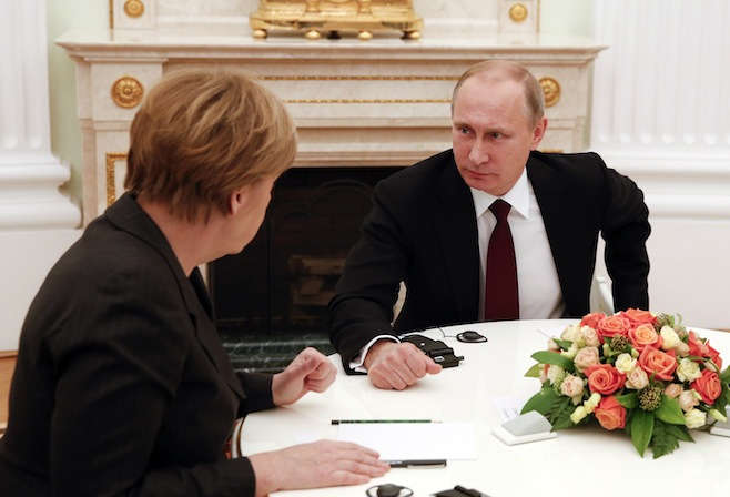 Russia's President Putin listens to German Chancellor Merkel during a meeting on resolving the Ukraine crisis at the Kremlin in Moscow