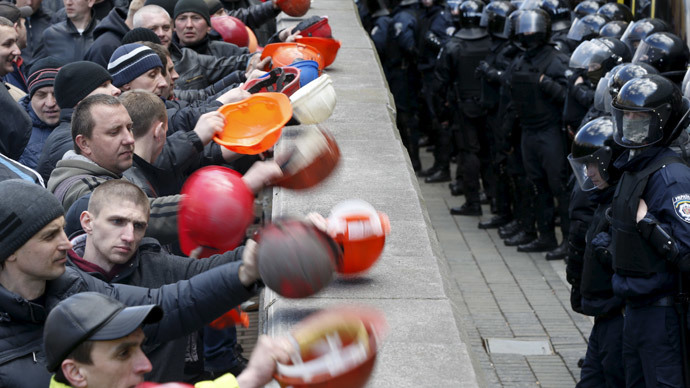 Miners bang their helmets on a barrier during a rally to demand the payment of their salaries in front of the government headquarters in Kiev April 22, 2015. (Reuters / Valentyn Ogirenko)