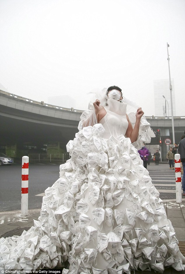 Artist Kong Ning wears a dress covered with breathing masks at Beijing Railway Station in the