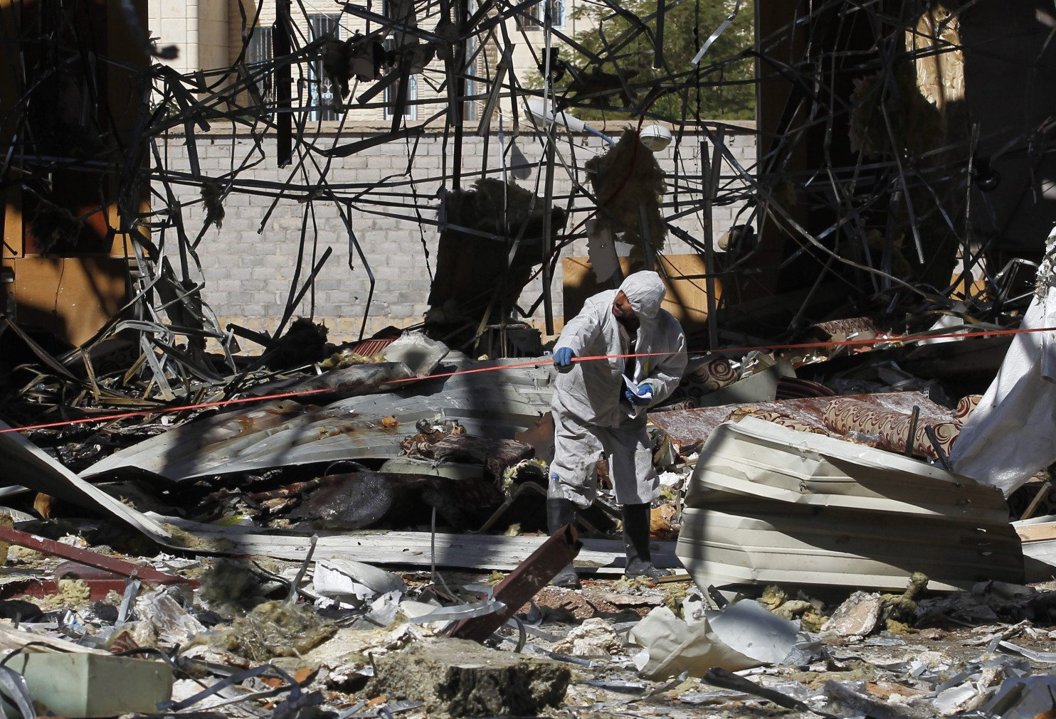 A forensic expert investigates the scene at a funeral hall on Oct. 10, two days after Saudi-led airstrikes hit it in Sanaa, Yemen. (Yahya Arhab/European Pressphoto Agency)