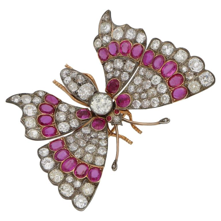 A stunning butterfly brooch set in 18ct rose gold and silver, featuring sprung set fluttering wings grain set with diamonds and rubies. The body of the butterfly is grain set with diamonds, featuring one large 1.44ct Old European cut diamond in the centre and with cabochon cut ruby eyes and diamond set antennae. The brooch measures 62mm in width and 40mm in length with a tube hinge pin and C-shaped safety clasp. The total diamond weight is approximately 17.20 cts, H/I colour and Si clarity, and the total ruby weight is approximately 6.00 cts, reddish purple 4/5 (GIA) and Si clarity. Gross weight: 25.50 grams.