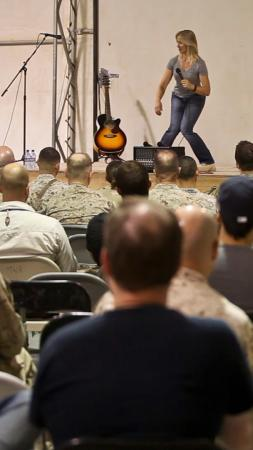 Lang Parker, comedian and fitness instructor, performs at the Town Hall, during the Armed with Laughter: Soul-dier Boot Camp Comedy Tour aboard Camp Leatherneck, Afghanistan, Sept. 23. Armed with Laughter was organized by Armed Forces Entertainment, which brought together four comedians who also taught different fitness courses.