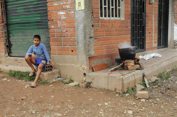A boy sits on a cement block around the corner from a large pot cooking on a fire, in a poor neighborhood in Medellin, Colombia.