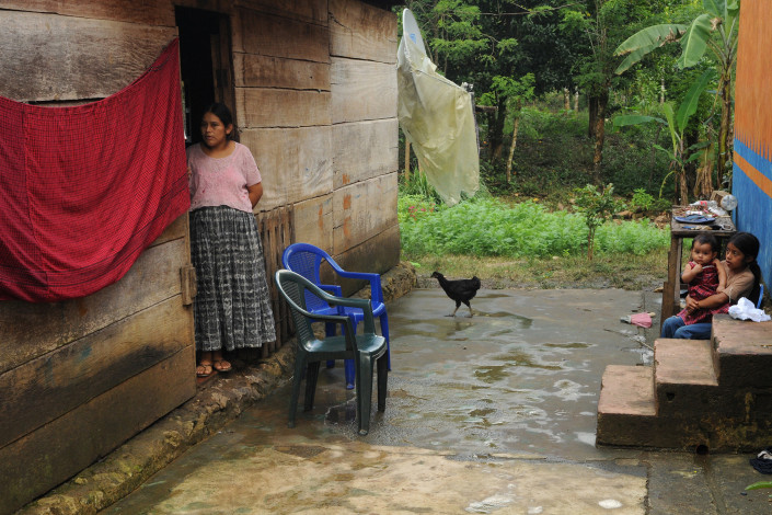 An indigenous Mayan woman and 2 children stand outside their home with a rooster nearby, in rural Guatemala.