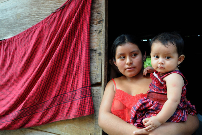 An indigenous Mayan woman holds her daughter outside their home in rural Guatemala while waiting for a community health worker.