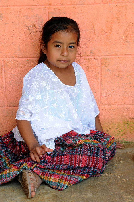 An indigenous Mayan girl sits outside a health center in rural Guatemala.