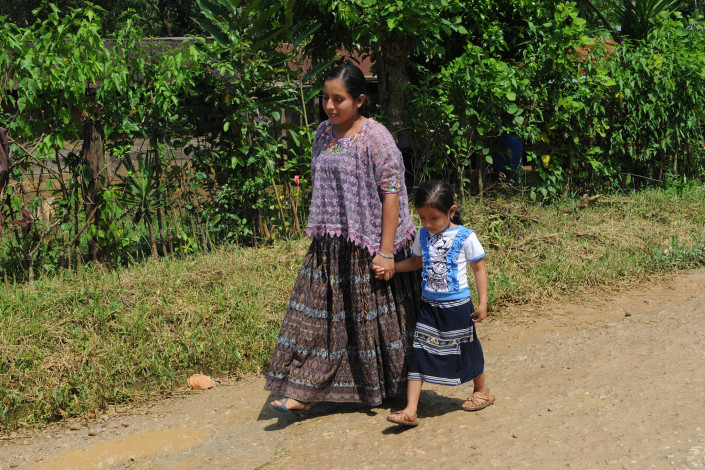 A pregnant indigenous Mayan woman walks home along a rural road, with her young daughter, after a visit to a health center.