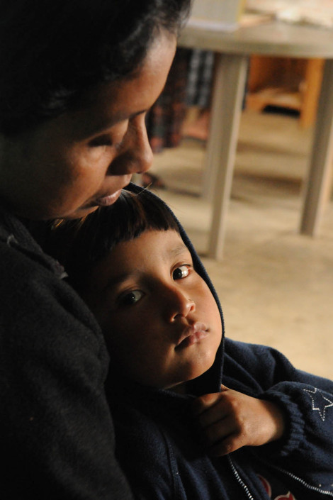 An indigenous Mayan woman holds her son at a rural health center while waiting for services, in rural Guatemala.
