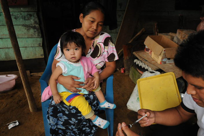 An indigenous Mayan woman holds her 1-year-old daughter as a volunteer health worker prepares a syringe with measles vaccine in rural Guatemala.
