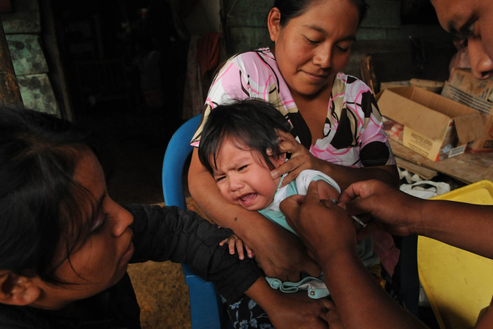 An indigenous Mayan woman holds her 1-year-old crying daughter as a volunteer health worker administers a measles vaccination in rural Guatemala.