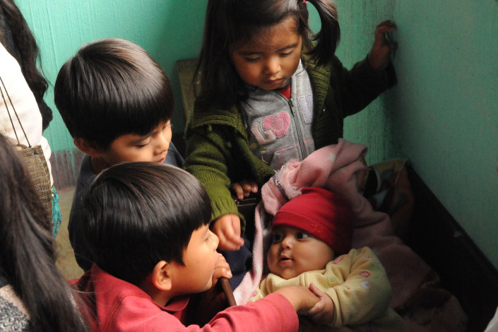 Children play with a baby lying in a makeshift crib at a health center in a rural community in Guatemala.