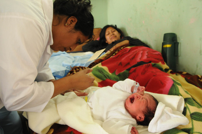 A mother winces as a newborn baby cries as a nurse administers a tuberculosis vaccination at a hospital in Guatemala.