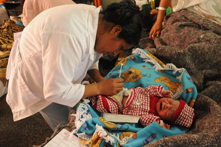 A nurse immunizes a 1-day-old infant boy against Hepatitis B, in a maternity ward in Coban, Guatemala.