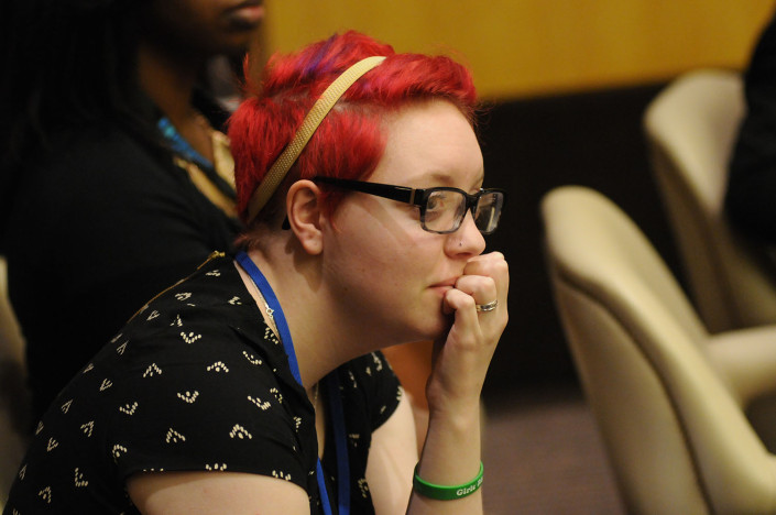 A woman with red hair listens during at meeting at the United Nations.