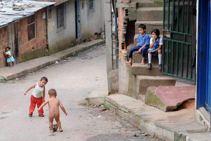 Small children play football as others watch nearby, in a poor neighborhood in Medellin, Colombia.