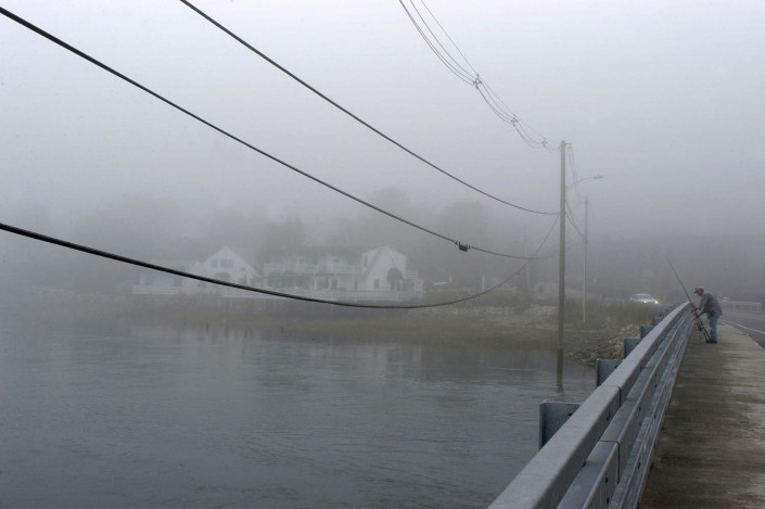 A man fishes off a street in Ogunquit, Maine.