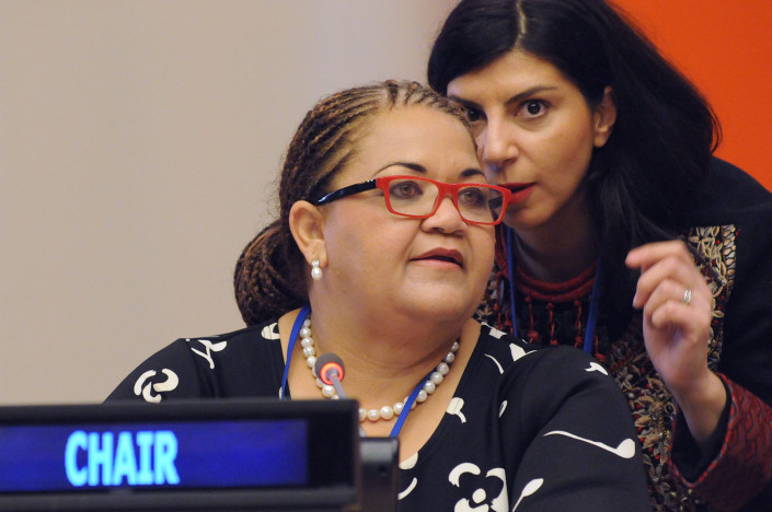 Women confer privately at a meeting at the United Nations.