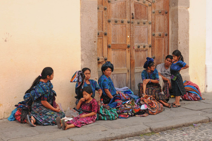 A group of women and children sit on a street in Antigua, Guatemala.