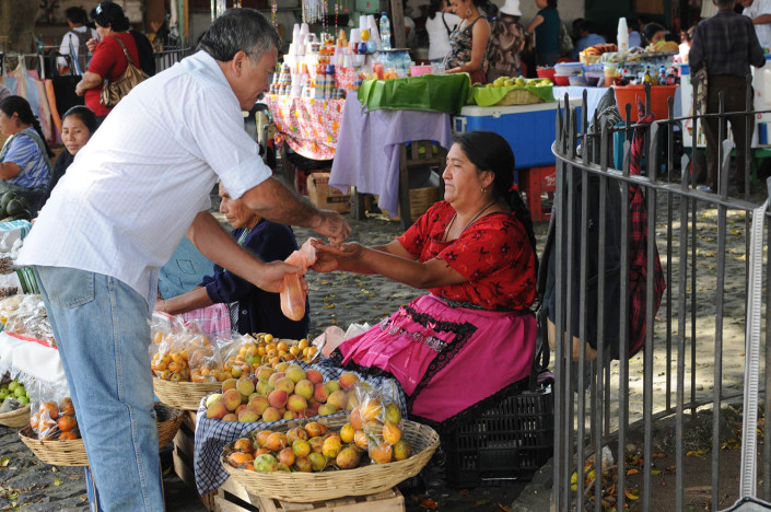 A woman sells fruit at a market in Antigua, Guatemala.