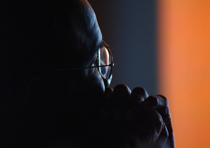 A man backlit by a film screen watches a documentary.