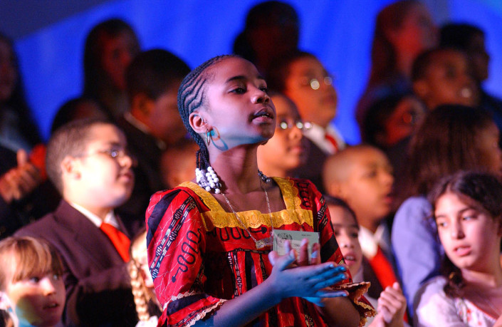 A girls sings during a choral performance.