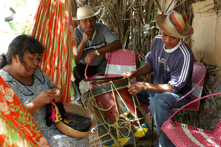 Indigenous Wayuu adolescent prepares musical instruments for a traditional dance.