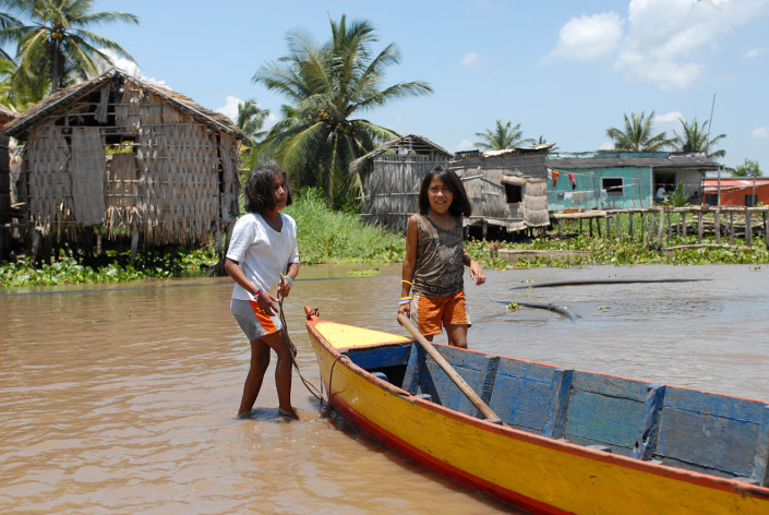 Indigenous Añu girls, standing next to a colorful canoe, play in a lagoon outside their home in Laguna de Sinamaica, Venezuela.