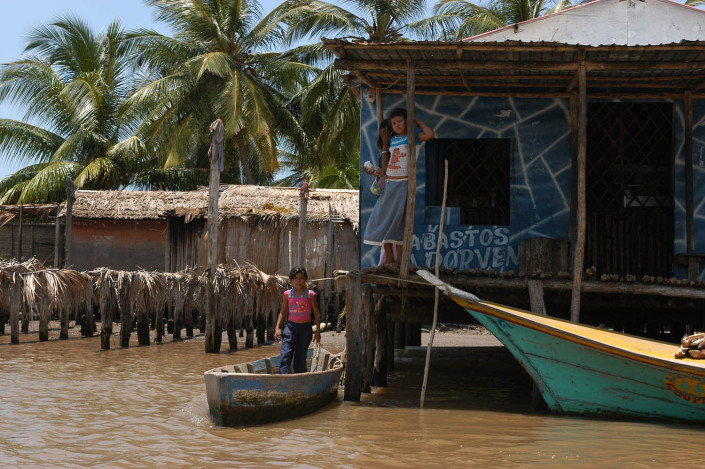 Indigenous Anu siblings stand outside their home, one in a boat, the other above a lagoon, in Laguna de Sinamaica, Venezuela.