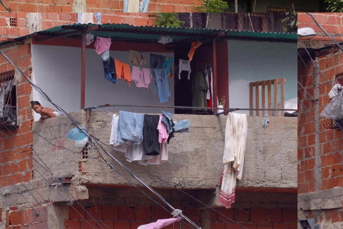 Laundry hangs from a balcony, as a girl leans over the side, in a poor neighborhood of Caracas, Venezuela.