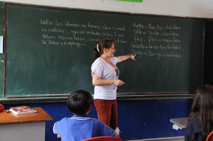 A teacher points to the blackboard during a Spanish class for third-graders in Medellín, Colombia.