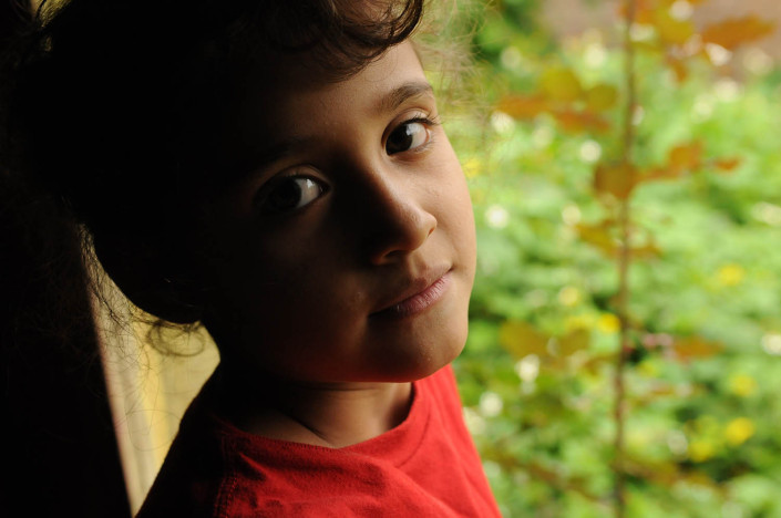 A girl stands in front of a window in her foster home in Guatemala.