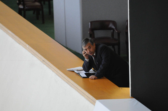 A man speaking on his cell phone, leans on a leather folder on a high ledge at the United Nations.