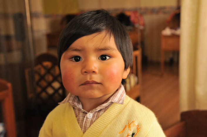 A boy stands in a crib at a shelter in Potosí, Bolivia.