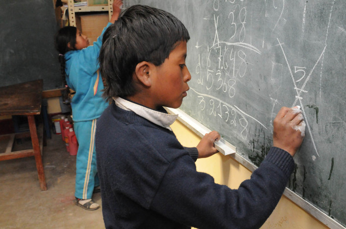 Children write on the blackboard at a school at the Cerro Rico Mines in Potosí, Bolivia.