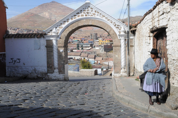 A woman stands on a sidewalk in the City of Potosí, Bolivia. Cerro Rico Mines are behind her.