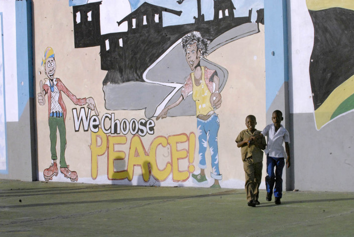 """Children walk outside a painted mural that says """"Peace Initiative."""""""