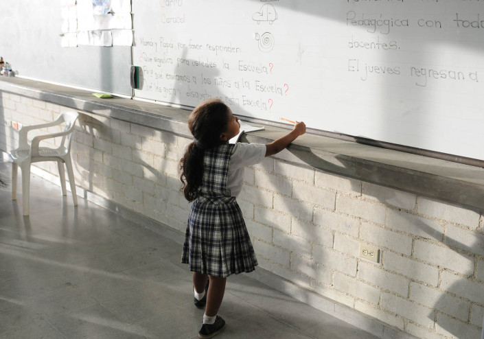 A first grade girl copies homework from the blackboard in Medellín, Colombia.