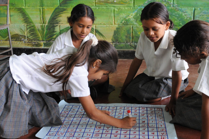 Girls play a word game on the floor, writing words in red marker, on a large sheet of paper in Lorica, Colombia.