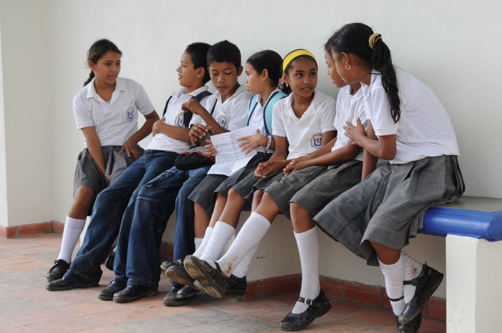 Girls and boys chat with each other outside their classroom in Lorica, Colombia.