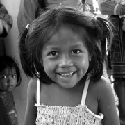 A smiling indigenous Shipibo Conibo girl stands outside a community center near her home in the Peruvian Amazon.