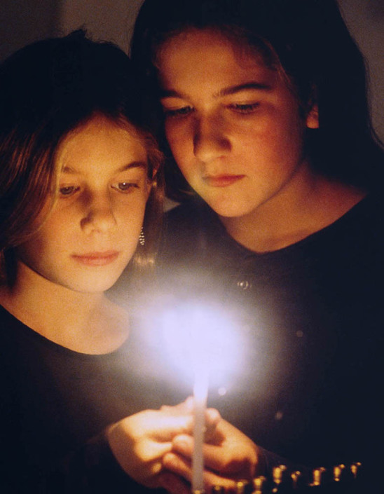 Photograph of sisters Jenny and Danielle lighting a menorah.