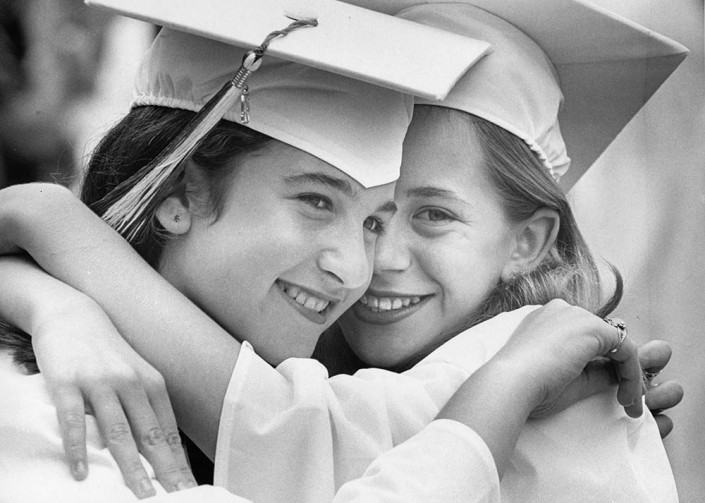 Sisters Danielle and Jennifer Avedon wearing white graduation caps and gowns embrace.