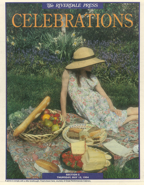 Tear sheet of a newspaper section on Celebrations featuring a girl seated on a colorful blanket with breads, cheeses and fruits.